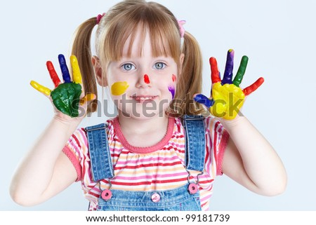 Girl having fun, her face and palms being covered with paint - stock photo