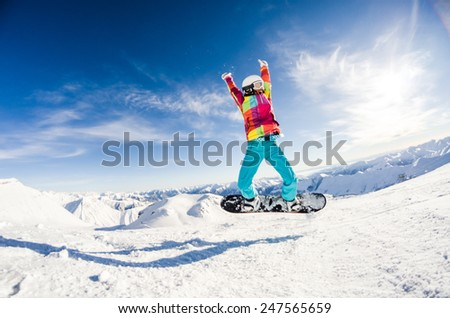 Girl having fun on her snowboard jumping - stock photo