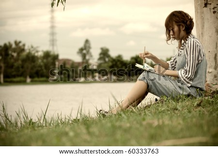 Girl having rest and drawing in the lake.