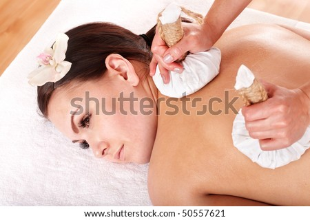Girl  having Thai herb compress massage in beauty spa. Body care. - stock photo