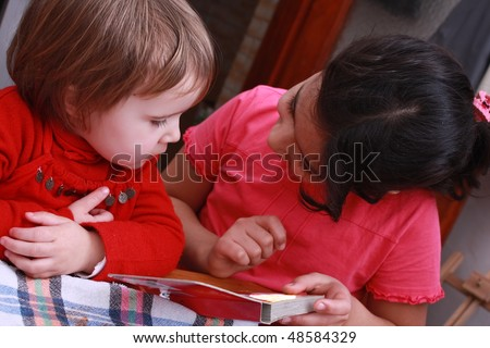 Girl helping younger sister to read - stock photo