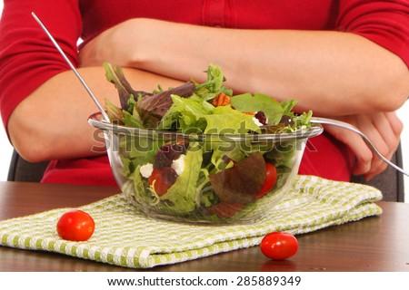 Girl hesitantly eating a leaf of lettuce - stock photo