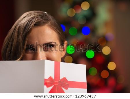 Girl hiding behind Christmas postcard - stock photo