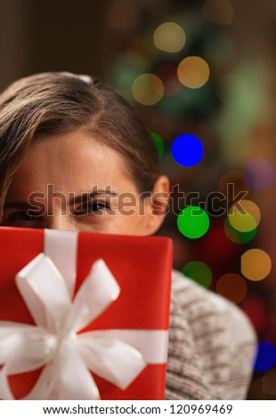 Girl hiding behind Christmas present box - stock photo