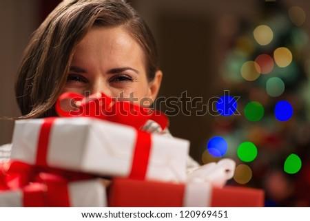Girl hiding behind Christmas present boxes - stock photo