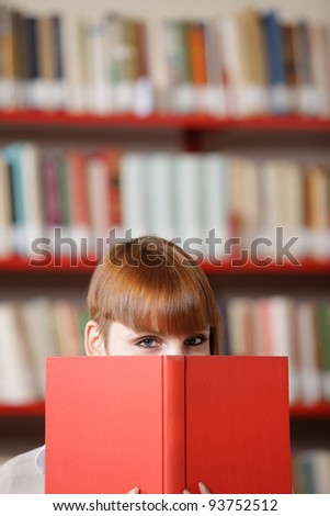 Girl hiding behind the book, bookshelf on background - stock photo