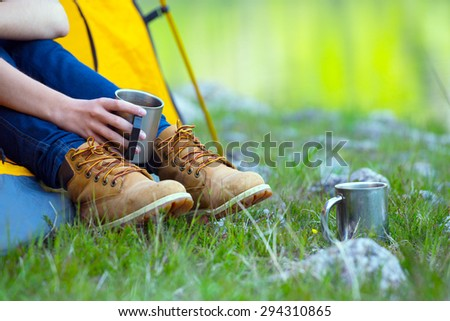 girl hiker in a tent and holding a cup  - stock photo