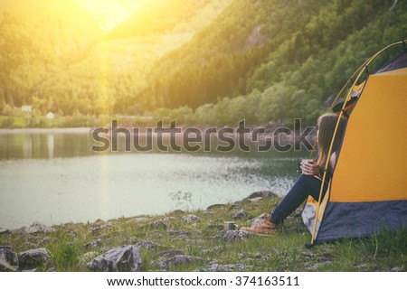 girl hiker in a tent and holding a cup mountains in the background