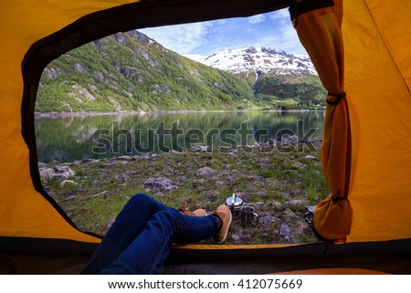 girl hiker in a tent and view of tent on the mountain, norway - stock photo