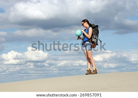 girl hiker looking at a globe where they will travel - stock photo