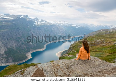 girl hiker looking at the fjord - stock photo