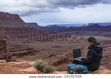 Girl Hiker on top of the mountain with her laptop computer - stock photo