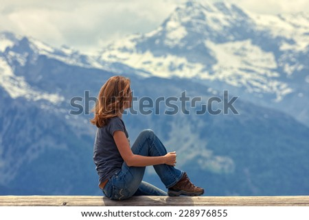 girl hiker sitting and looking at the snowed mountains  - stock photo
