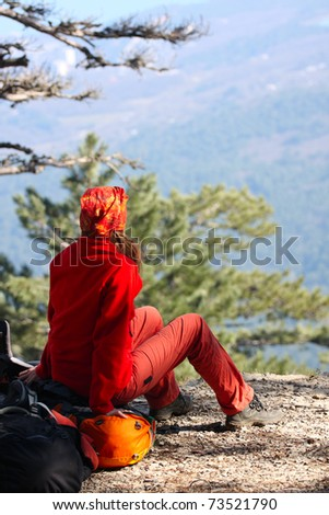girl hiker sitting on a rock and looking at the mountains