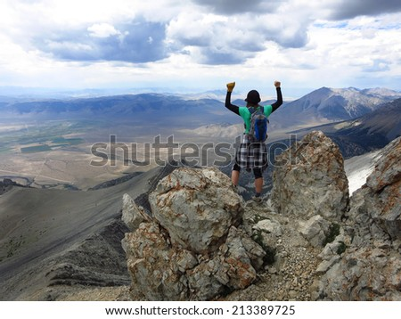 Girl hiker summit mountain top in triumph - stock photo
