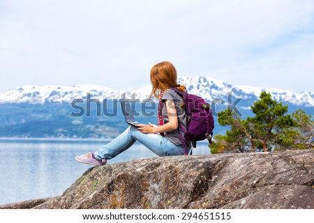 girl hikerl with a laptop sitting on a rock on a background of mountains and lakes