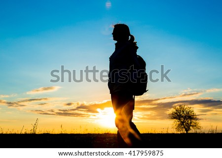 Girl hiking in silhouette in the sky colored
