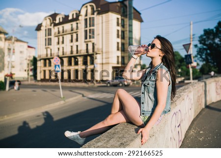 Girl hippie in the summer drinking water