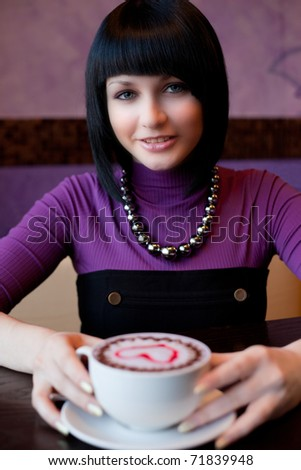 girl hold cup of coffee in hand and smiling - stock photo