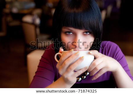 girl hold cup of coffee in hand look straight