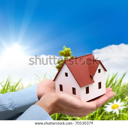 Girl hold house against green field - stock photo