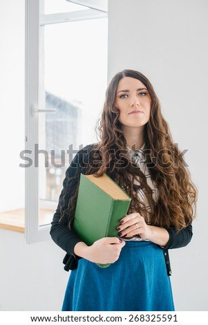 Girl holding a big old green book - stock photo