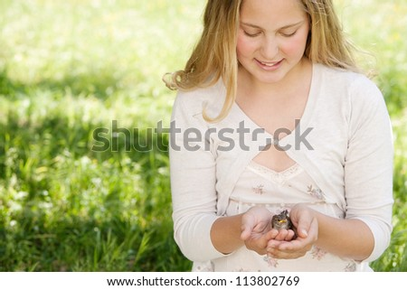 Girl holding a bird in her hands while sitting down on a long green grass garden, smiling. - stock photo