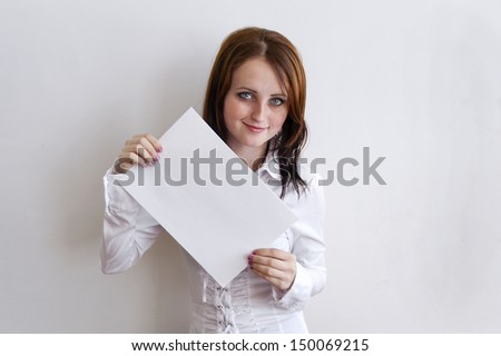 girl holding a blank sheet of paper with both hands and smiling - stock photo