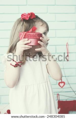 Girl holding a box near the ear - stock photo
