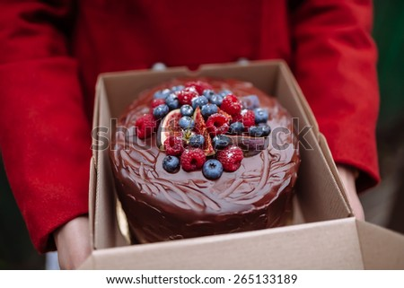girl holding a box of chocolate cake with berries - stock photo