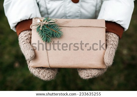 Girl holding a Christmas present in mittens - stock photo