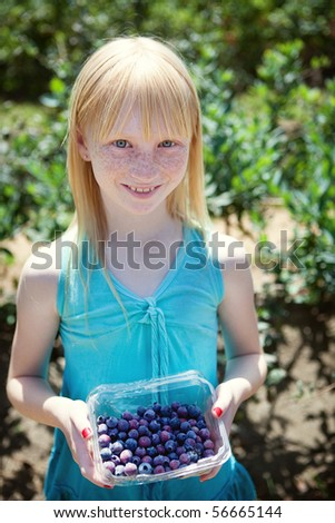 Girl holding a container of blueberries - stock photo