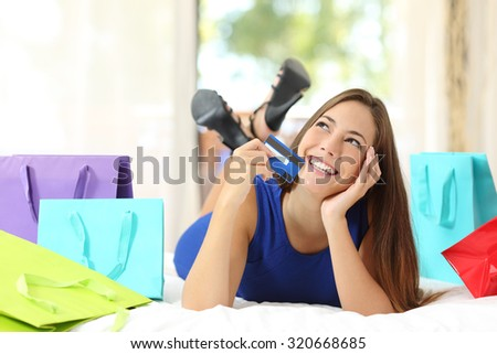 Girl holding a credit card thinking what to buy with colorful shopping bags beside and looking sideways at home - stock photo