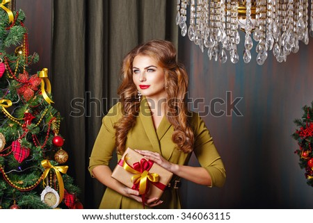 Girl holding a gift. Christmas tree. New Year. Waiting for a miracle. Merry Christmas. 2017 - stock photo