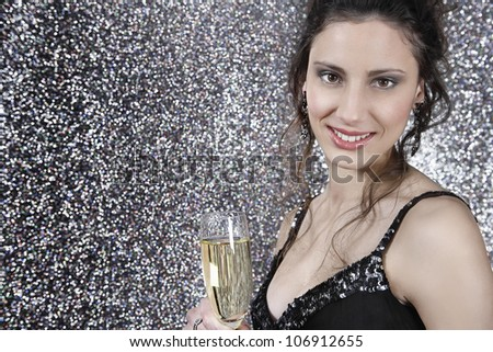 Girl holding a glass of champage against a silver glitter background, smiling at camera.