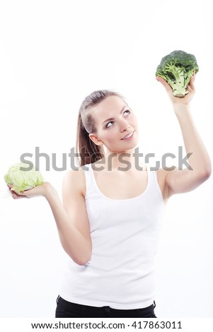 Girl holding a green cabbage and broccoli