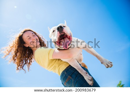 Girl holding a huge dog breed Staffordshire Terrier - stock photo