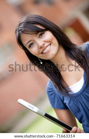 Girl holding a laptop computer outdoors and smiling - stock photo
