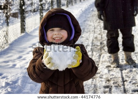 Girl holding a large chunk of snow, Germany