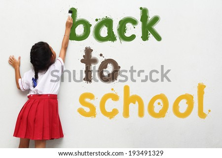girl holding a paint brush painting back to school text on wall - stock photo