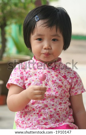 Girl holding a pink lolly pop - stock photo