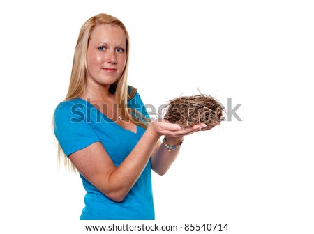 Girl holding a real bird's nest wearing a blue shirt on pure white background with room for copy.