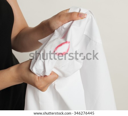 girl holding a shirt with the imprint of lipstick. - stock photo