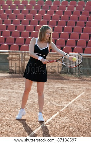 Girl holding a tennis racquet while standing on a tennis court for lessons. - stock photo