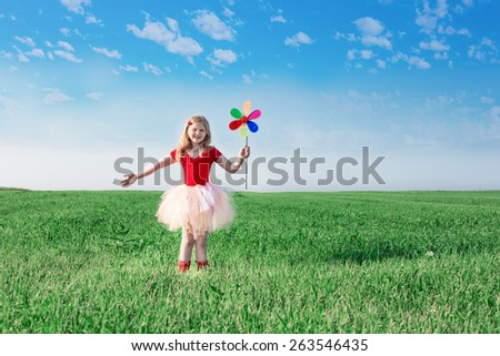 girl  holding a toy flower on background sky and field - stock photo