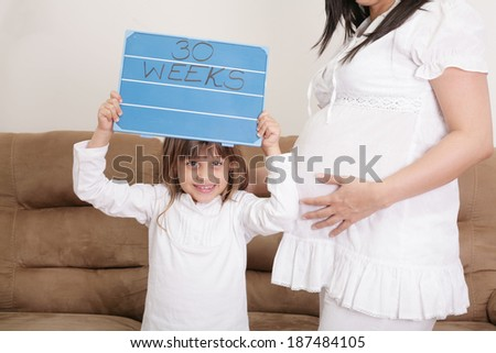 Girl holding a 30 weeks sign to her expectant mother - stock photo