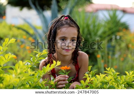 Girl holding a yellow flower in the garden