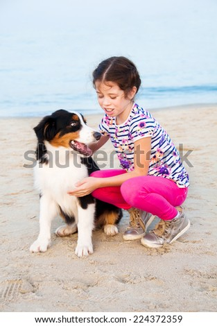 Girl holding an australian shepherd dog beside sea coast - stock photo