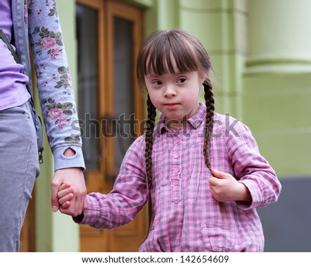 Girl holding arms of the mother on a walk . - stock photo