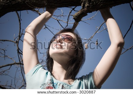 Girl holding at the branch and looking up.